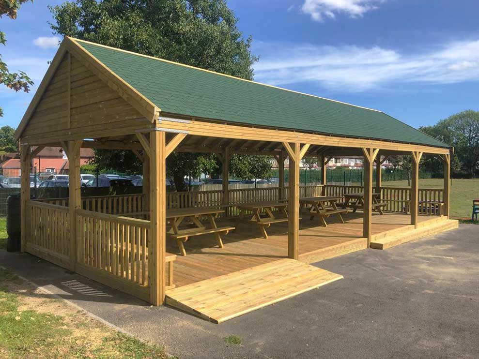 outdoor wooden shelter with benches installed at school playground 1